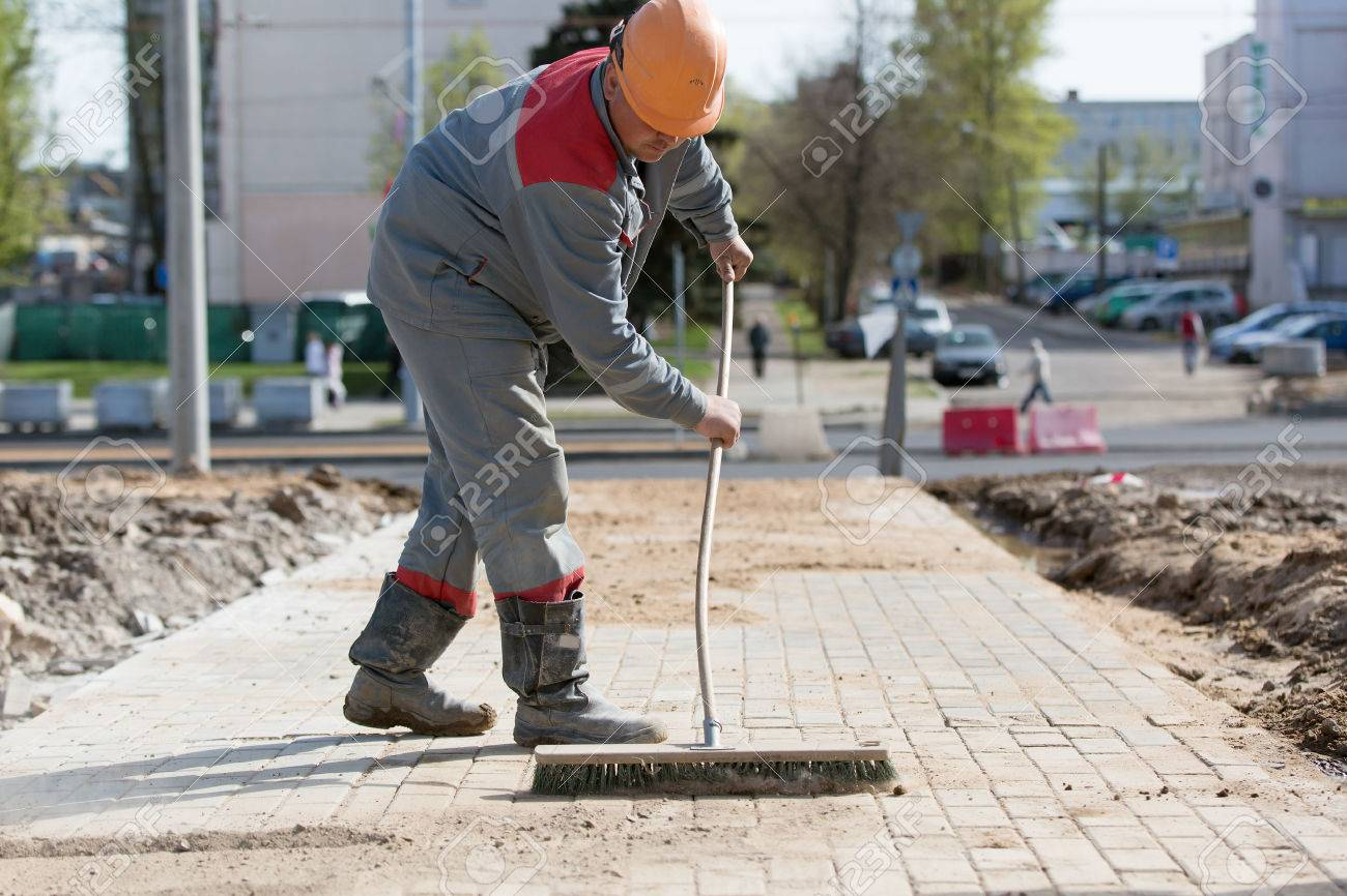 Construction worker grouting dry sand with brush into paver bricks joints during road works - 55641666