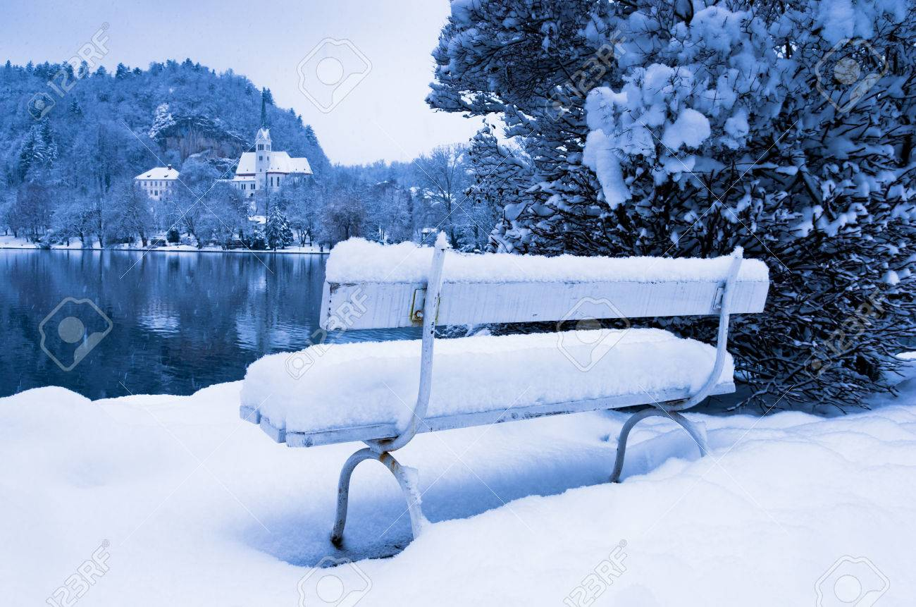 Romantic White Bench Covered With Snow On A Lake Bled In Slovenian
