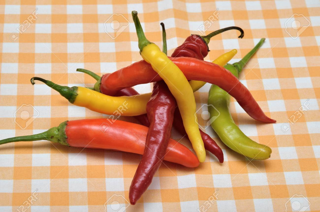 Pile Of Red, Orange, Green And Yellow Hot Chili Peppers On White Yellow