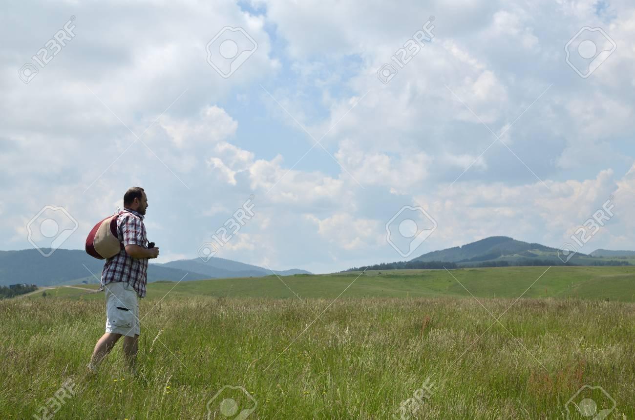 Man wanderer mit einem rucksack und fernglas auf einer wiese. hills