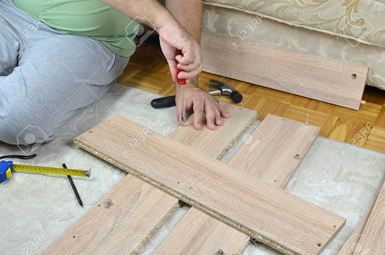Man Assembling A Drawer Of A New Cabinet With Diy Tools Stock Photo