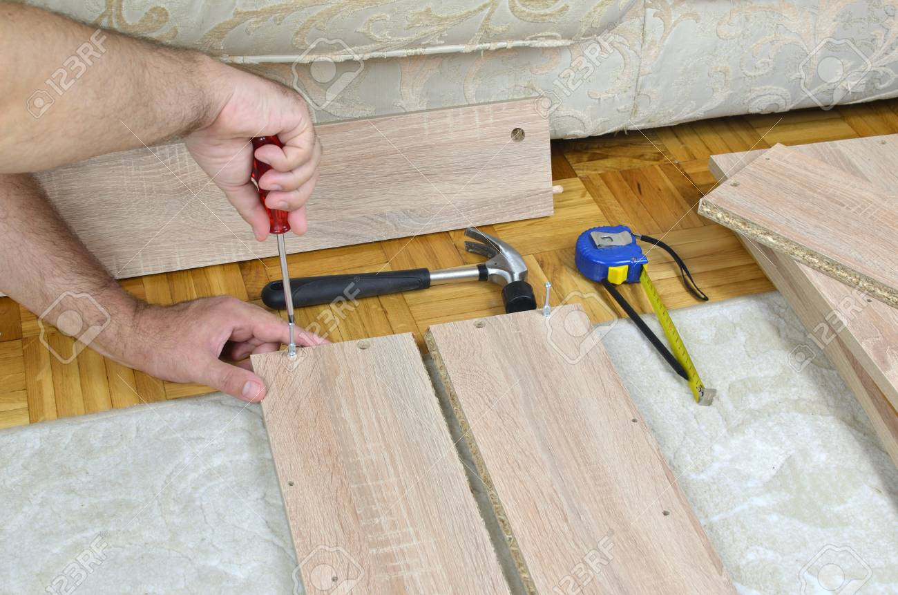 Man Assembling A Drawer Of A Cabinet With Diy Tools Stock Photo