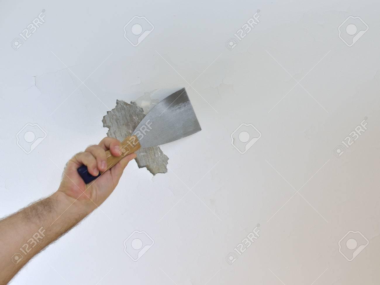 hand mit einem gipsspachtel, decken schaben, die vorbereitung es zum