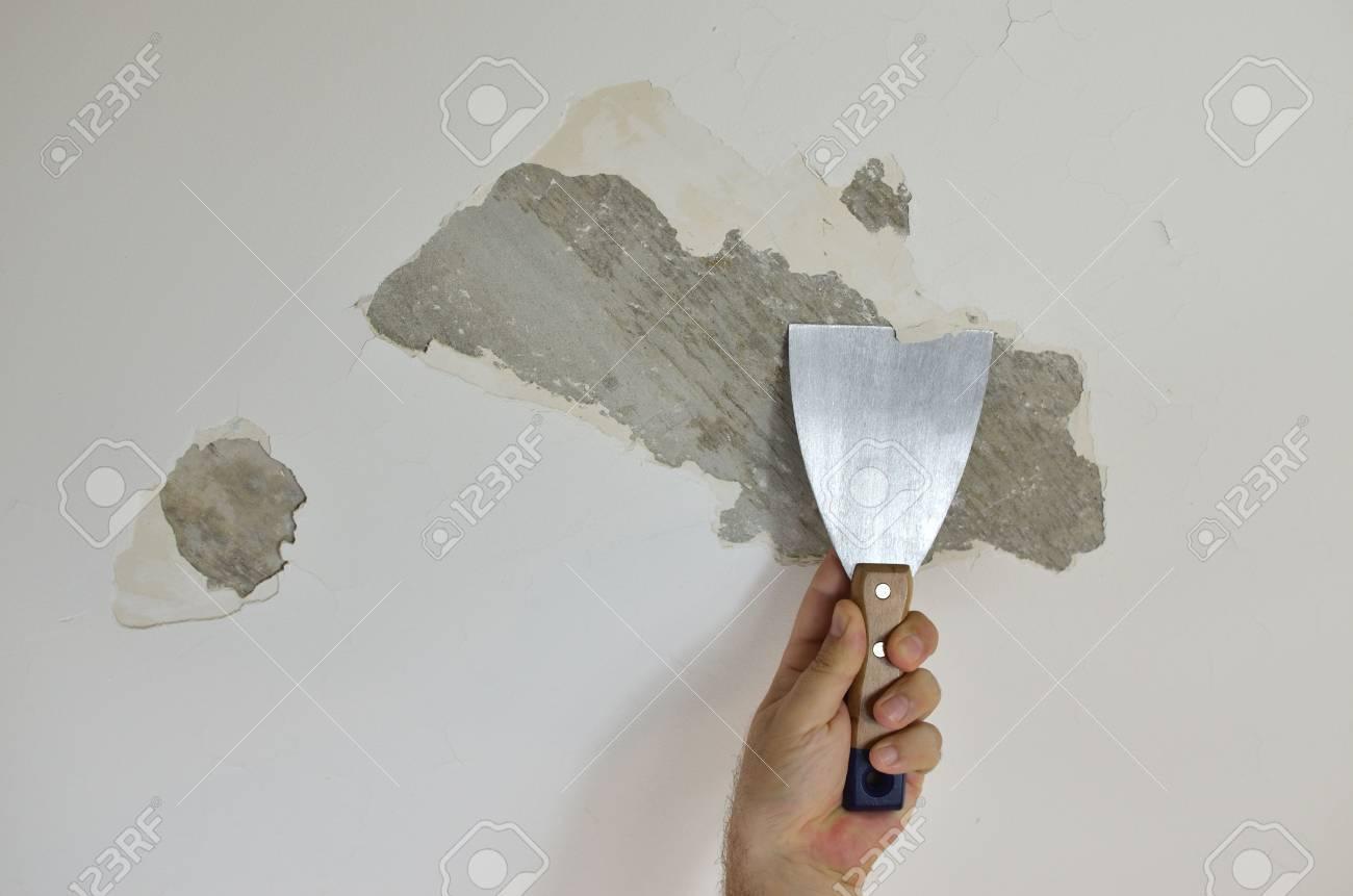 hand mit einem gipsspachtel, decken peeling, bereitet es zur