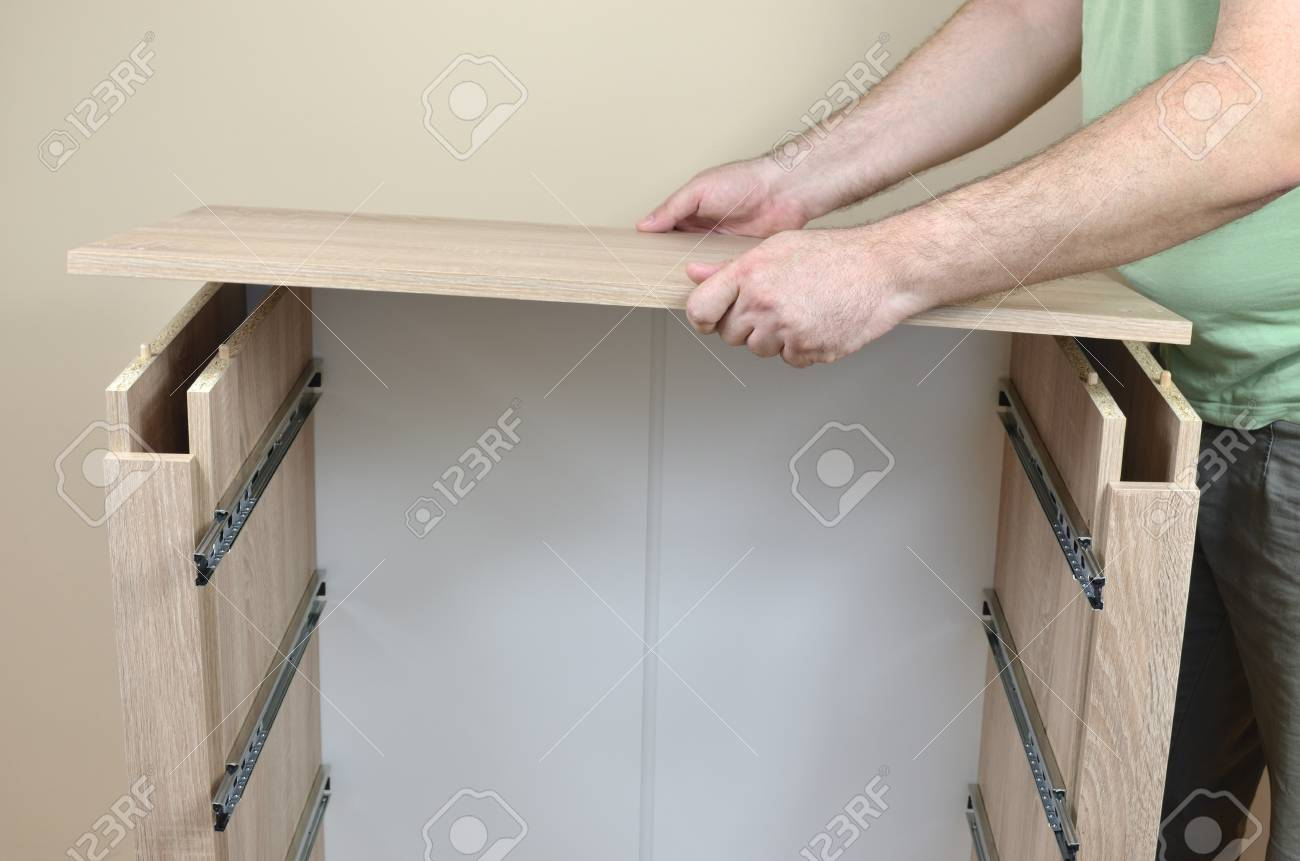 Man Assembling Parts Of A New Piece Of Furniture With Drawer Stock