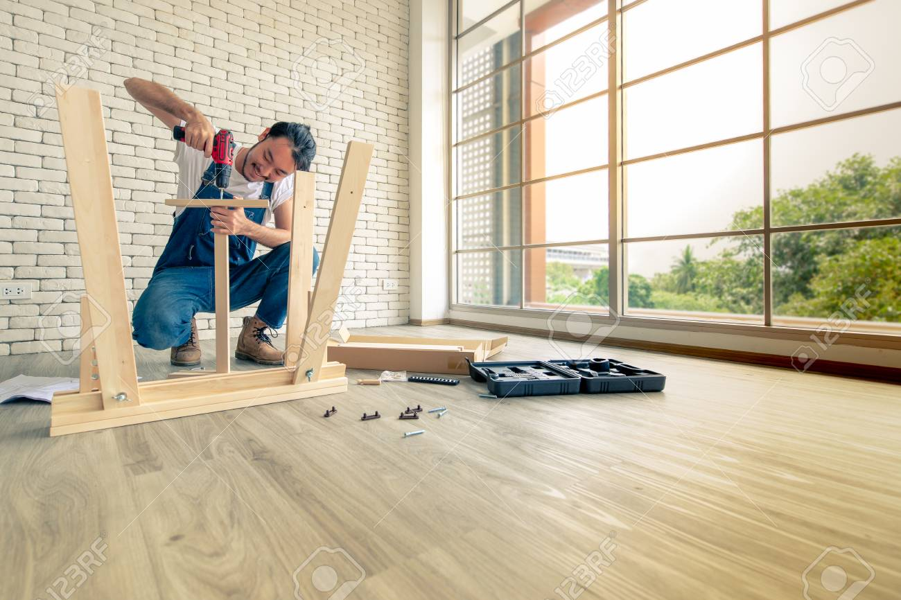 Young man working as handyman, assembling wood table with equipments, concept for home diy and self service.in the office there is a white brick block. - 107035493