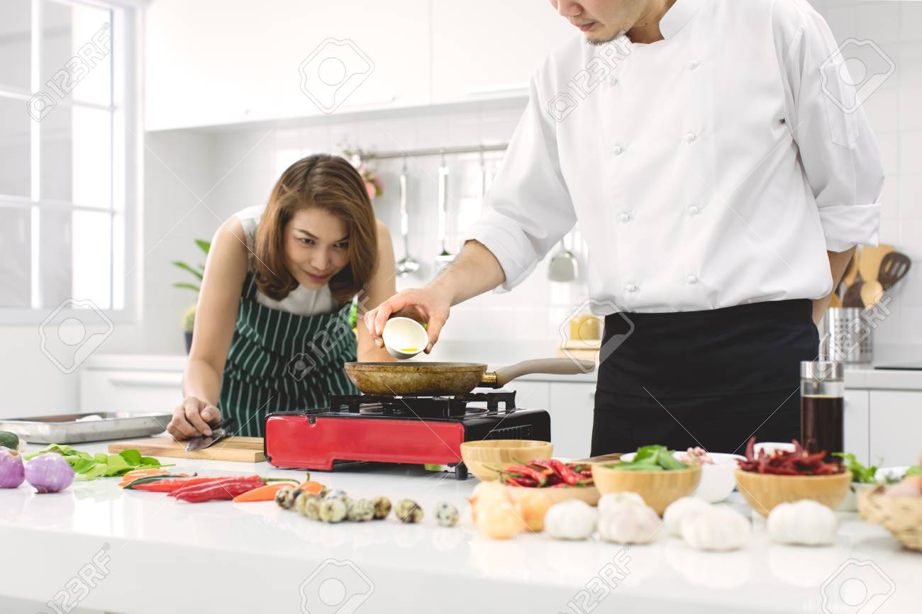 Beautiful Asian woman in red apron looking and noticing how to make fried egg, teaching by chef in white clean modern kitchen. - 112649619