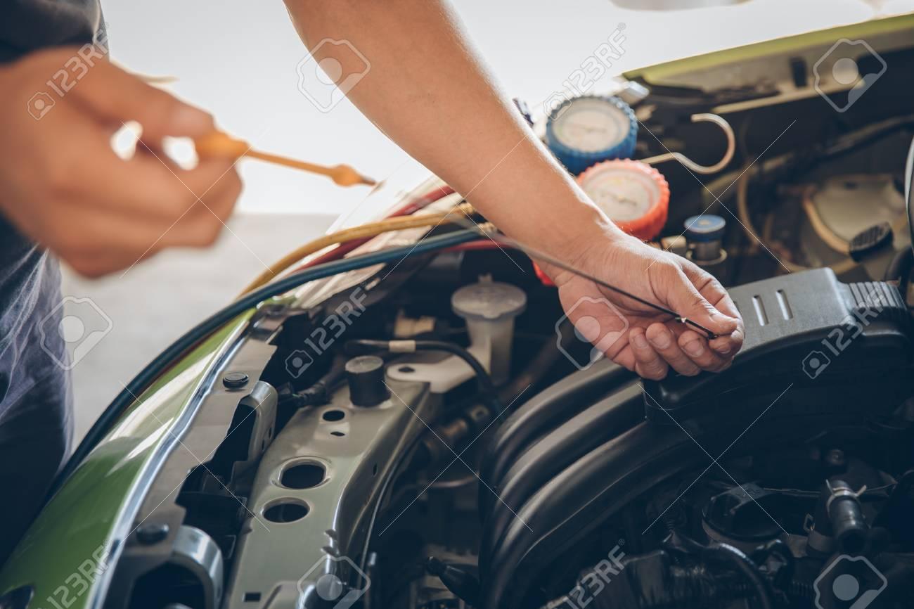 Auto mechanic checking oil - 125681302