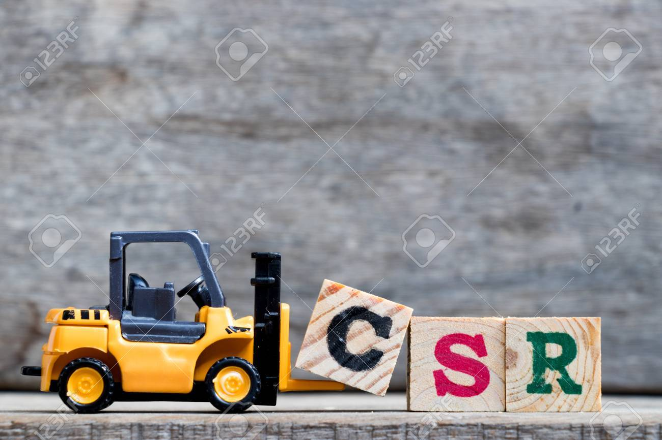 Yellow plastic forklift hold letter C to complete word CSR (Abbreviation from corporate social responsibility) on wood background - 89704806
