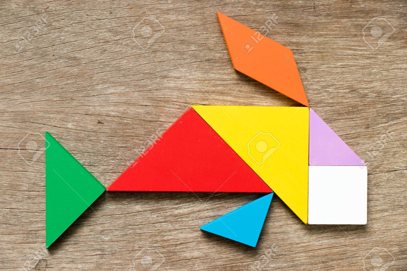 Colorful tangram puzzle in swimming fish or carp shape on wood background - 93688986