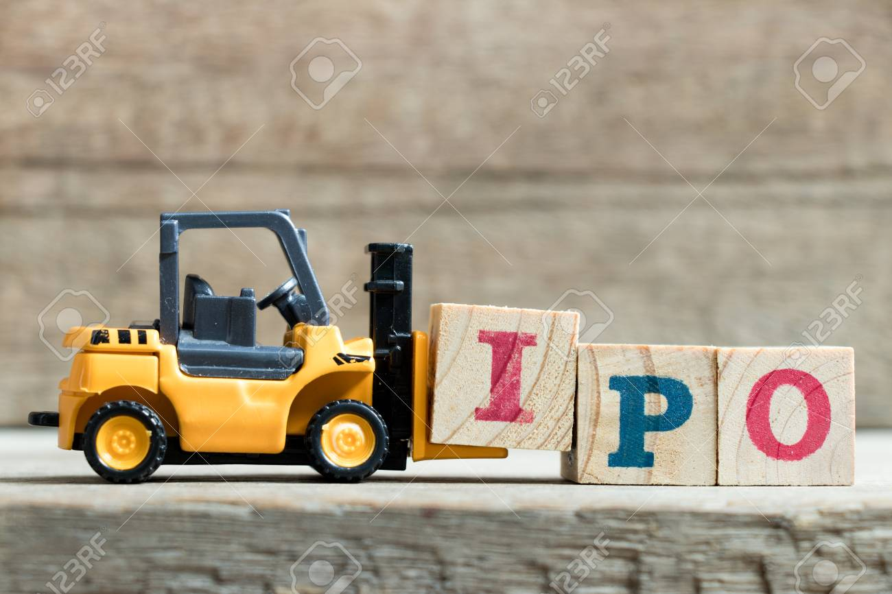 Toy yellow forklift hold letter block I to complete word IPO (Abbreviation of Initial Public Offering)on wood background - 94116100