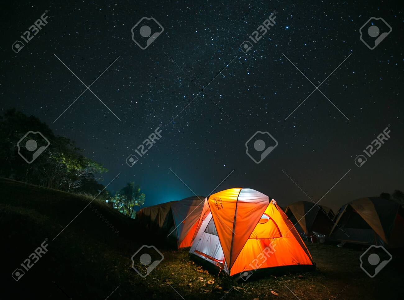 Traveling and camping concept - camp tent at night under a sky full of stars. - 141957333