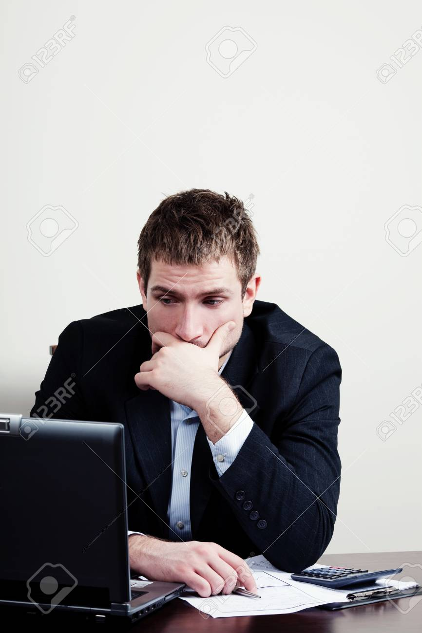 Sad Businessman Sitting Behind A Desk With A Laptop