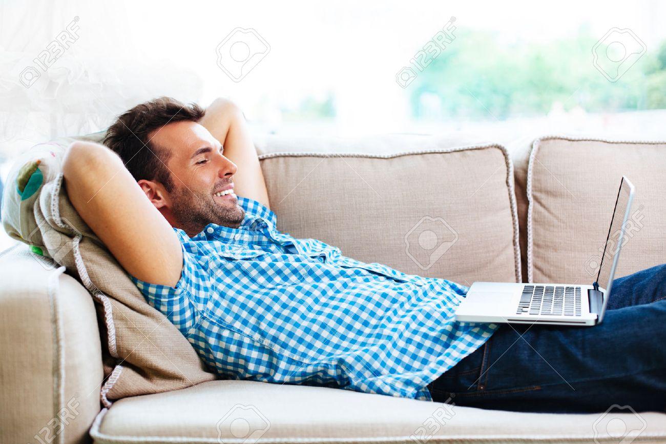 Mann mit Laptop sich entspannt auf der Couch Standard-Bild - 53952043