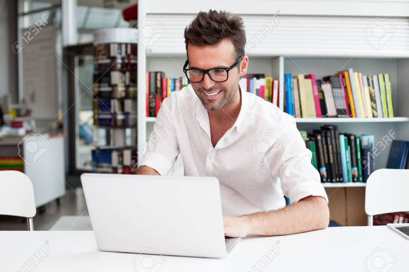 Happy man working on laptop in library Standard-Bild - 53952077