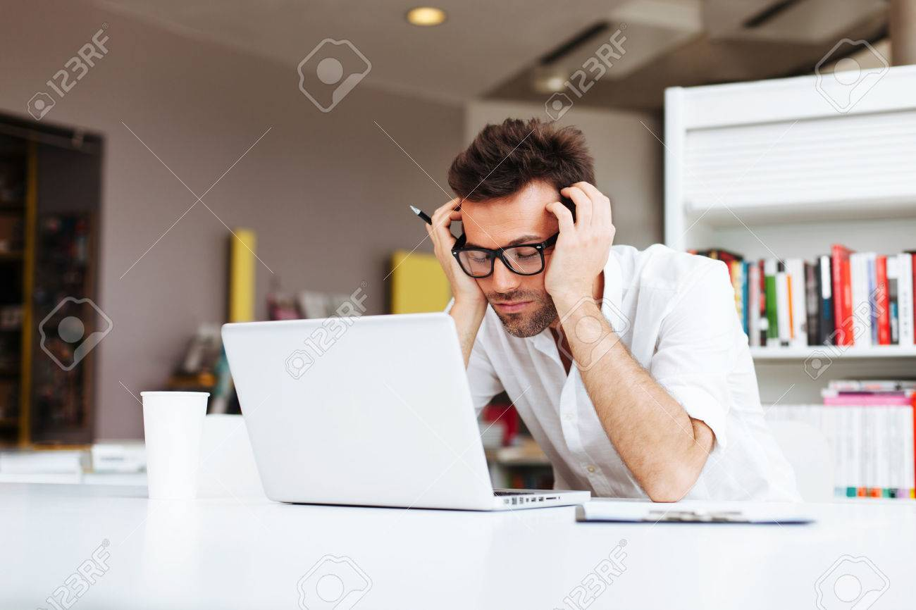 Tired student or businessman working with laptop in the office Standard-Bild - 53952220