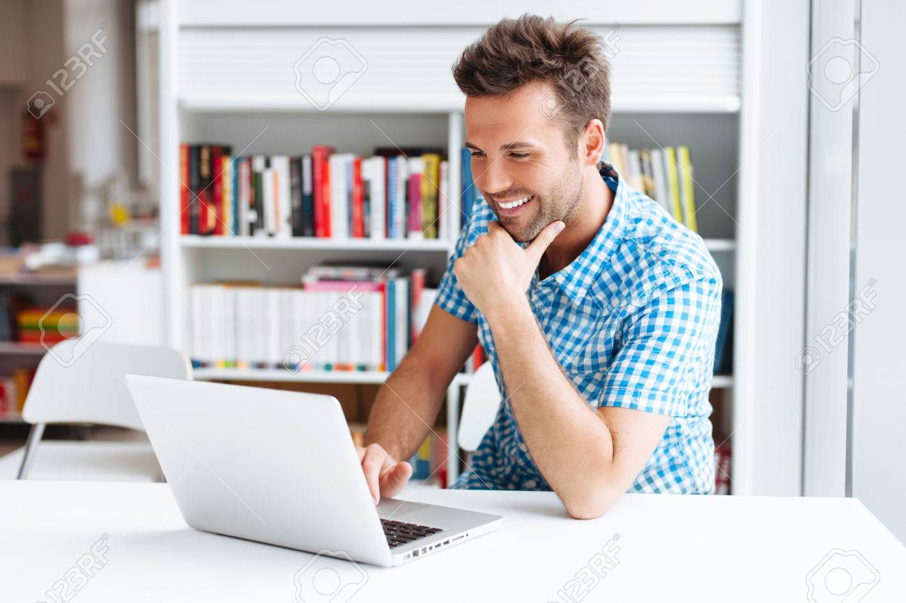 Casual man working on laptop in library Standard-Bild - 53952223