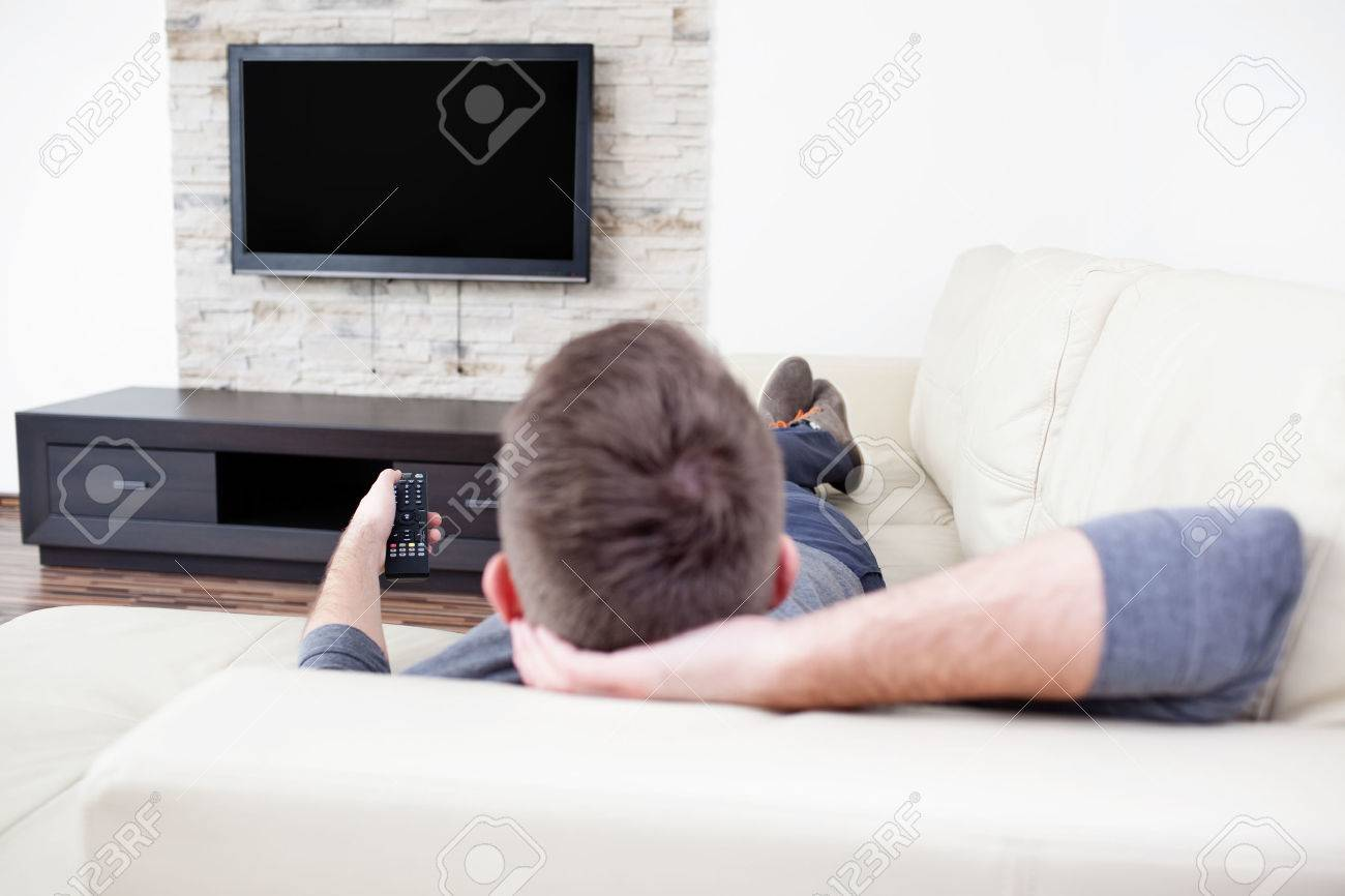 Single man on the couch watching tv, changing channels Standard-Bild - 53952552