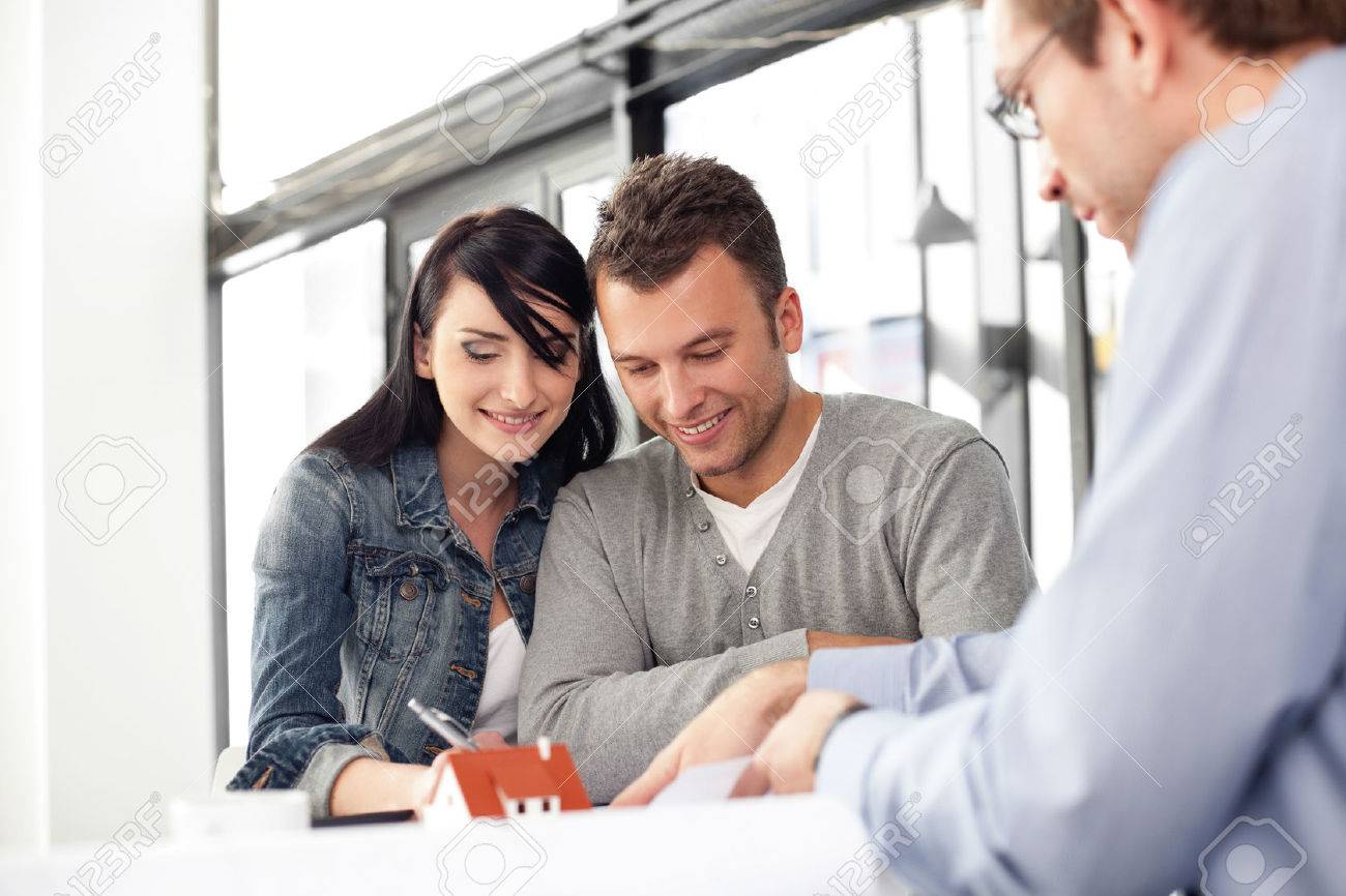 Young couple buying new home. Meeting with architect. Standard-Bild - 53952981