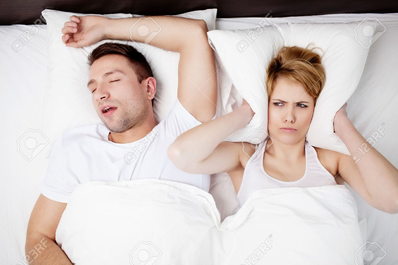 Snoring man and young woman. Couple sleeping in bed. Standard-Bild - 53952995