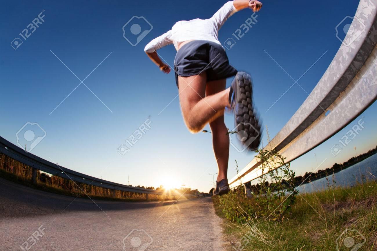 Man running fast on road during sunset. Standard-Bild - 53953350