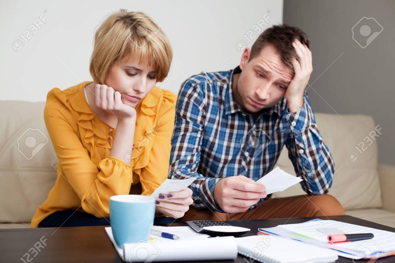Sad, depressed young couple paying bills. - 53953443