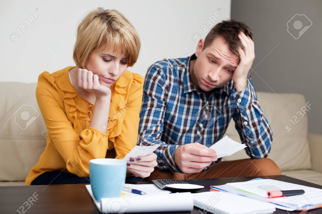 Sad, depressed young couple paying bills. Standard-Bild - 53953443