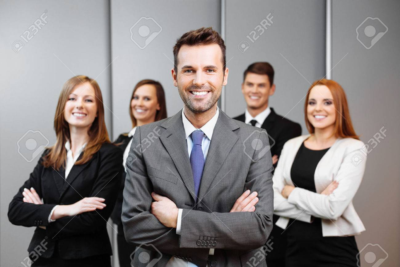 Team leader stands with coworkers in background - 53953561