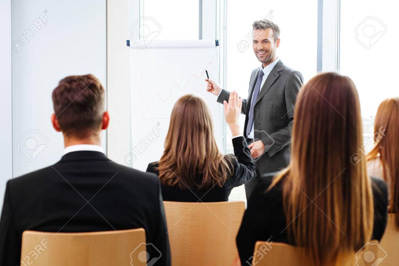 Businessman giving a presentation on flipchart. Teamwork concept - 53953629