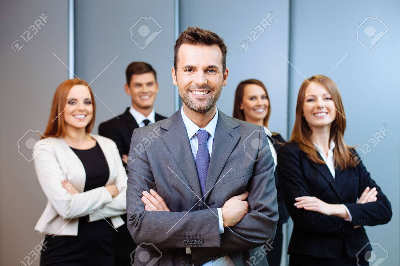 Team leader stands with coworkers in background Standard-Bild - 53953650