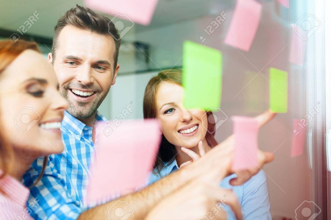 Group of corporate people working on new project with many sticky notes on window Standard-Bild - 53954723