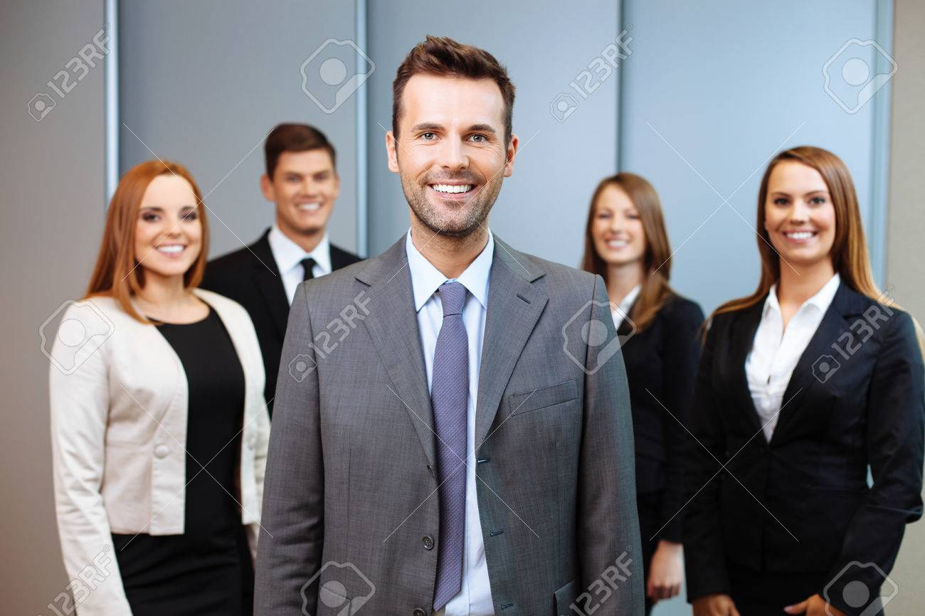 Group of business people with team leader in foreground - 53954761