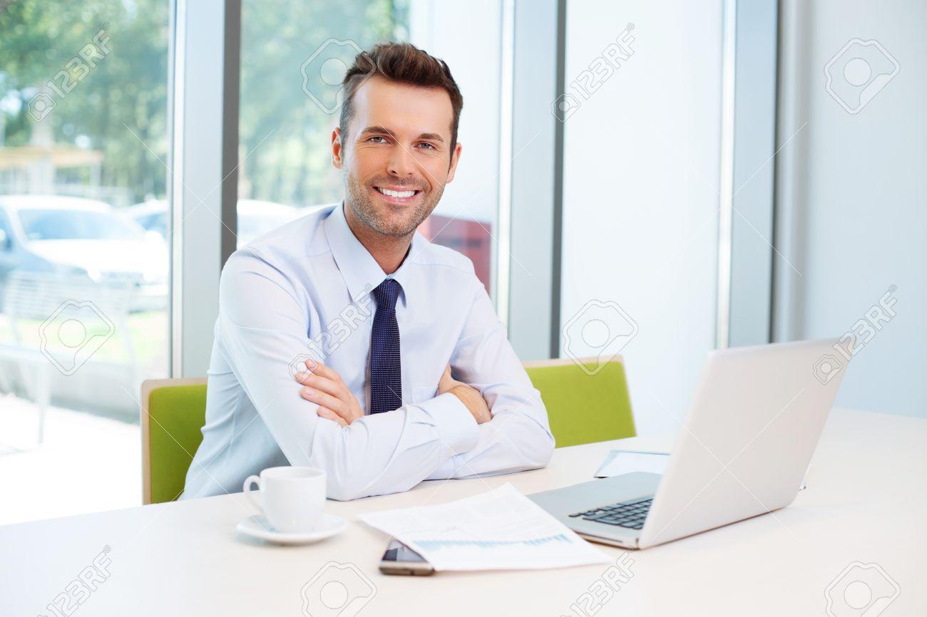 Happy man sitting at desk in the office Standard-Bild - 53957368