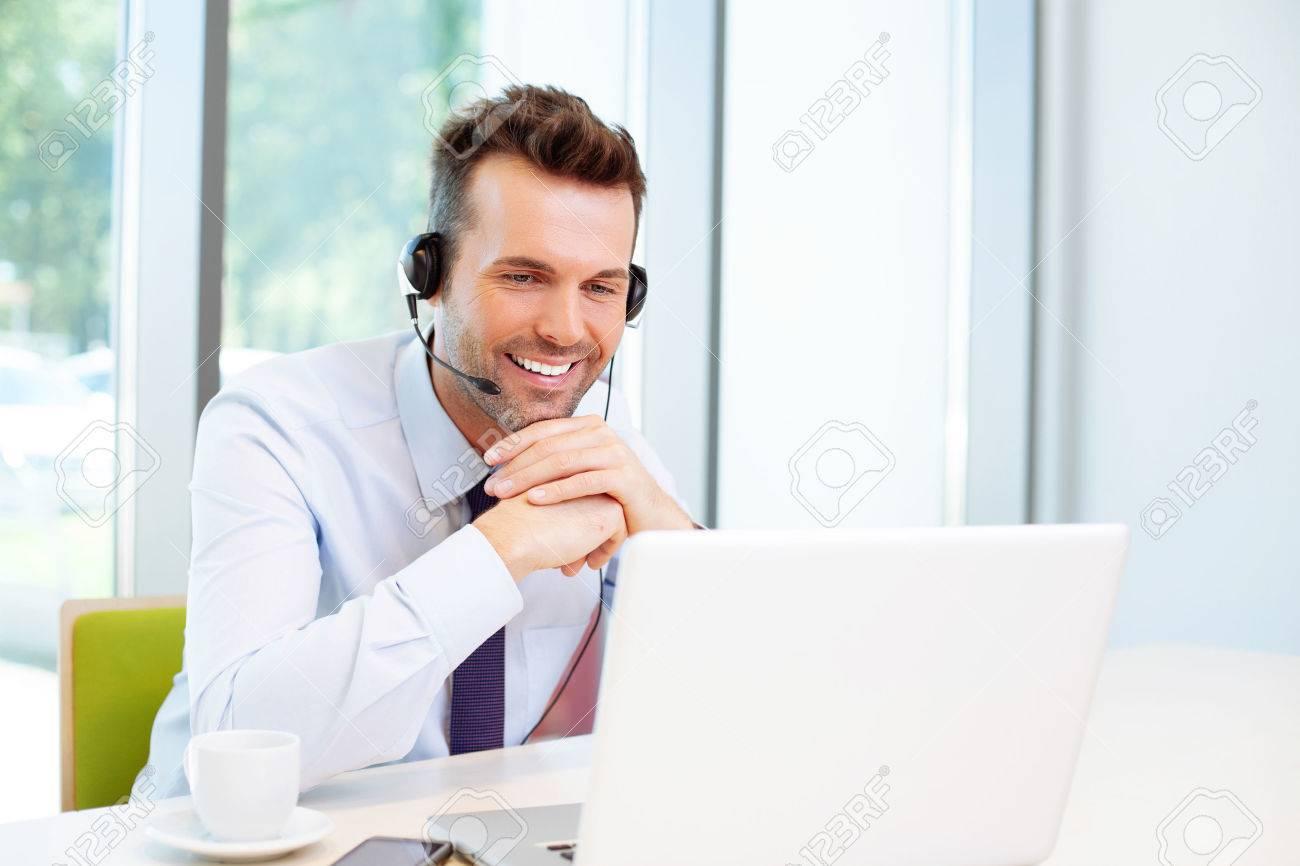 Glücklicher Berater mit Headset am Laptop Standard-Bild - 53957453