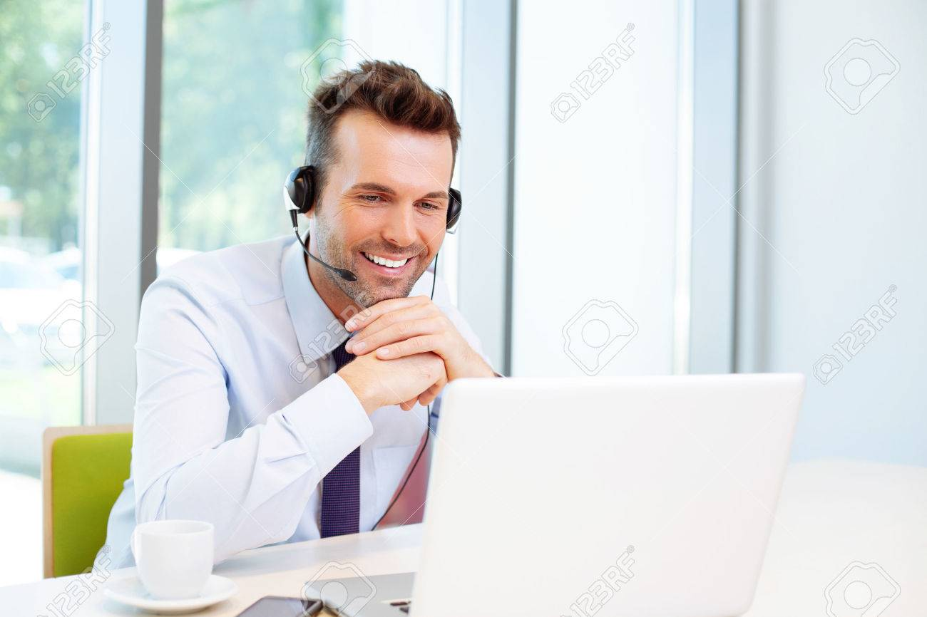 Happy consultant with headset looking at laptop Standard-Bild - 53957453