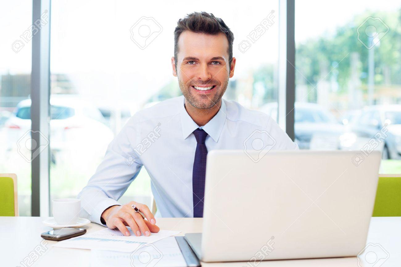 Glücklicher Geschäftsmann im Büro auf Laptop arbeitet. Standard-Bild - 53957477