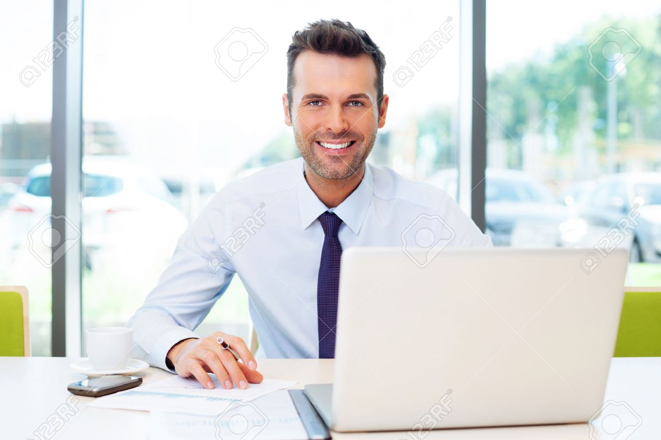 Happy businessman working at the office on laptop. Standard-Bild - 53957477