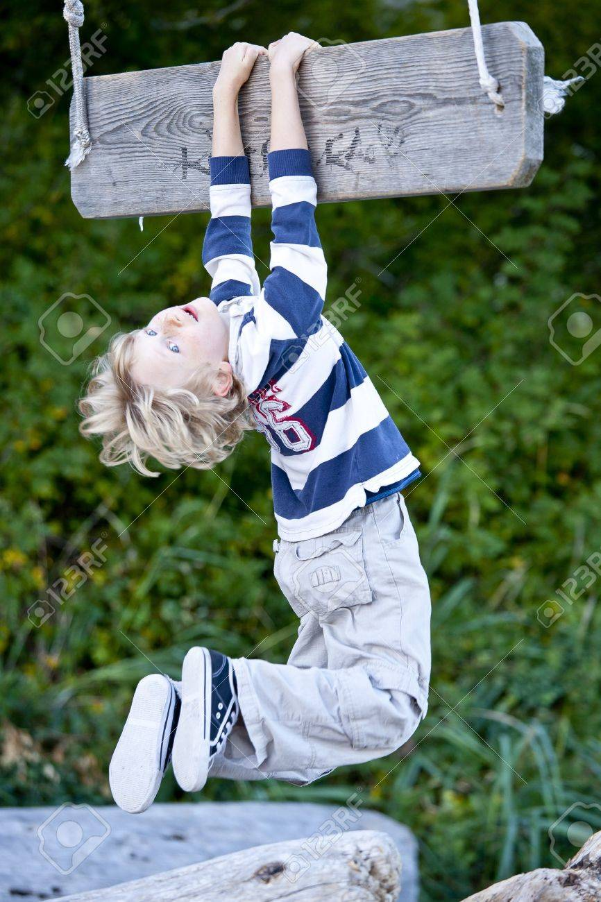 A young boy hanging from a swing . Stock Photo - 11333820