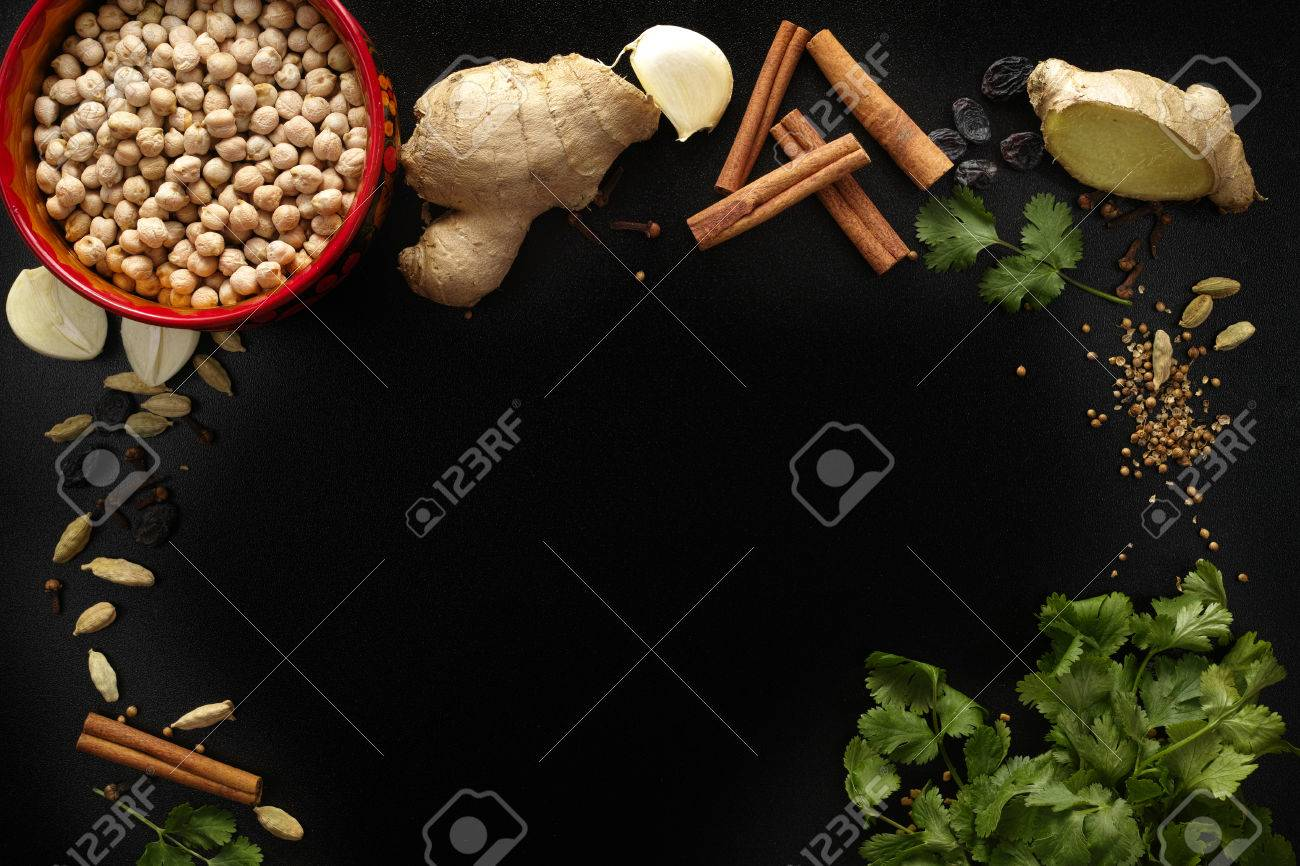 Indian spices, fresh coriander, ginger, garlic and dried cardamom, cloves, cinnamon on black background, copy space - 53236261