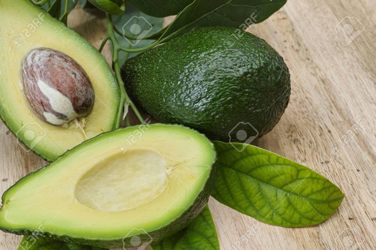 Fresh avocado with avocado leaves on teak wood table top - 53371383