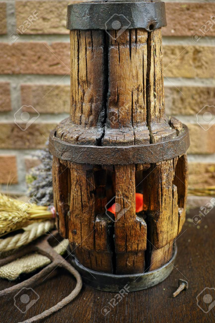 Antique Pitchfork And Wooden Wheel Hub Against Rural Brick Wall