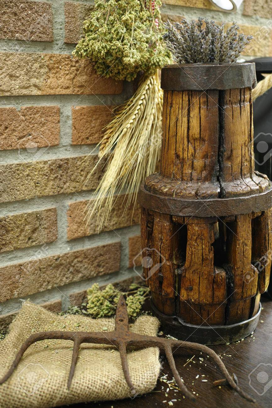 Antique Pitchfork And Wooden Wheel Hub On Burlap Sack Against