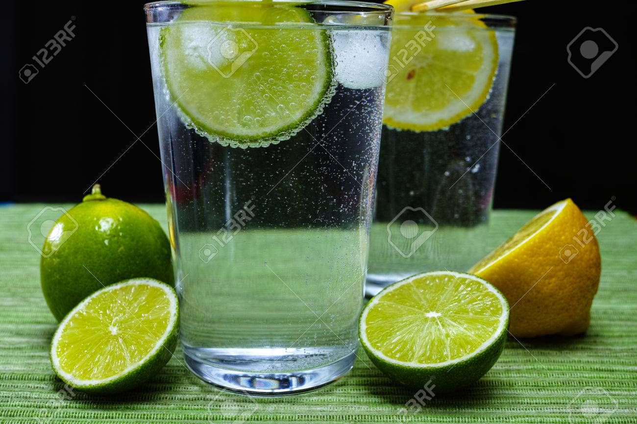 Glass with cold sparkling mineral water, lime and lemon, seltzer - 62115645
