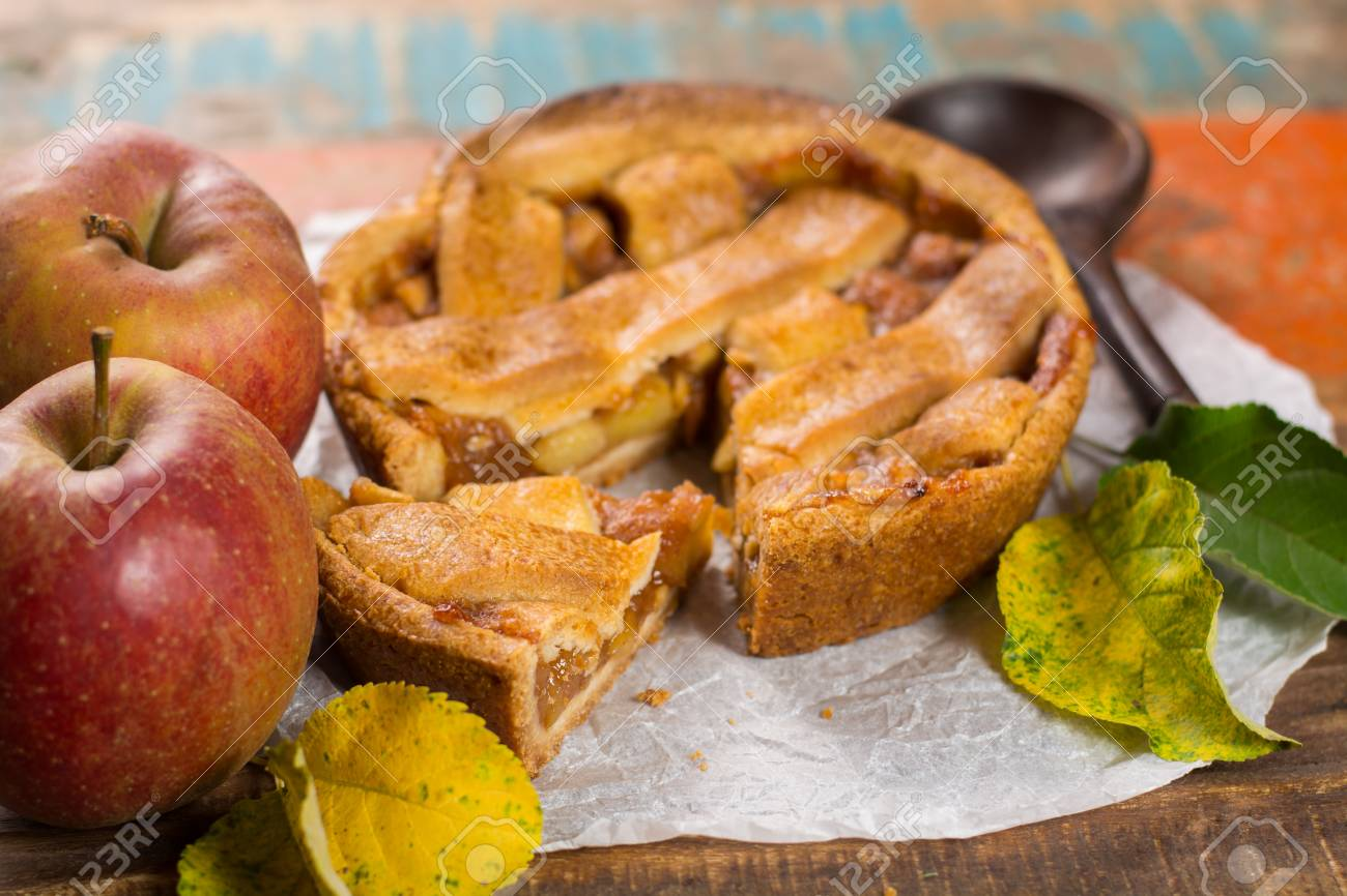 2d265fb178cd Stock Photo - Traditional homemade apple pie with nuts and cinnamon close  up and fresh ripe Golden Reinette apples on wooden table