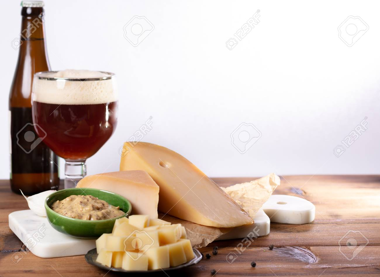finger food usually served with glass of beer, cubes hard old Dutch cow and goat cheese with Dijon mustard - 108564133