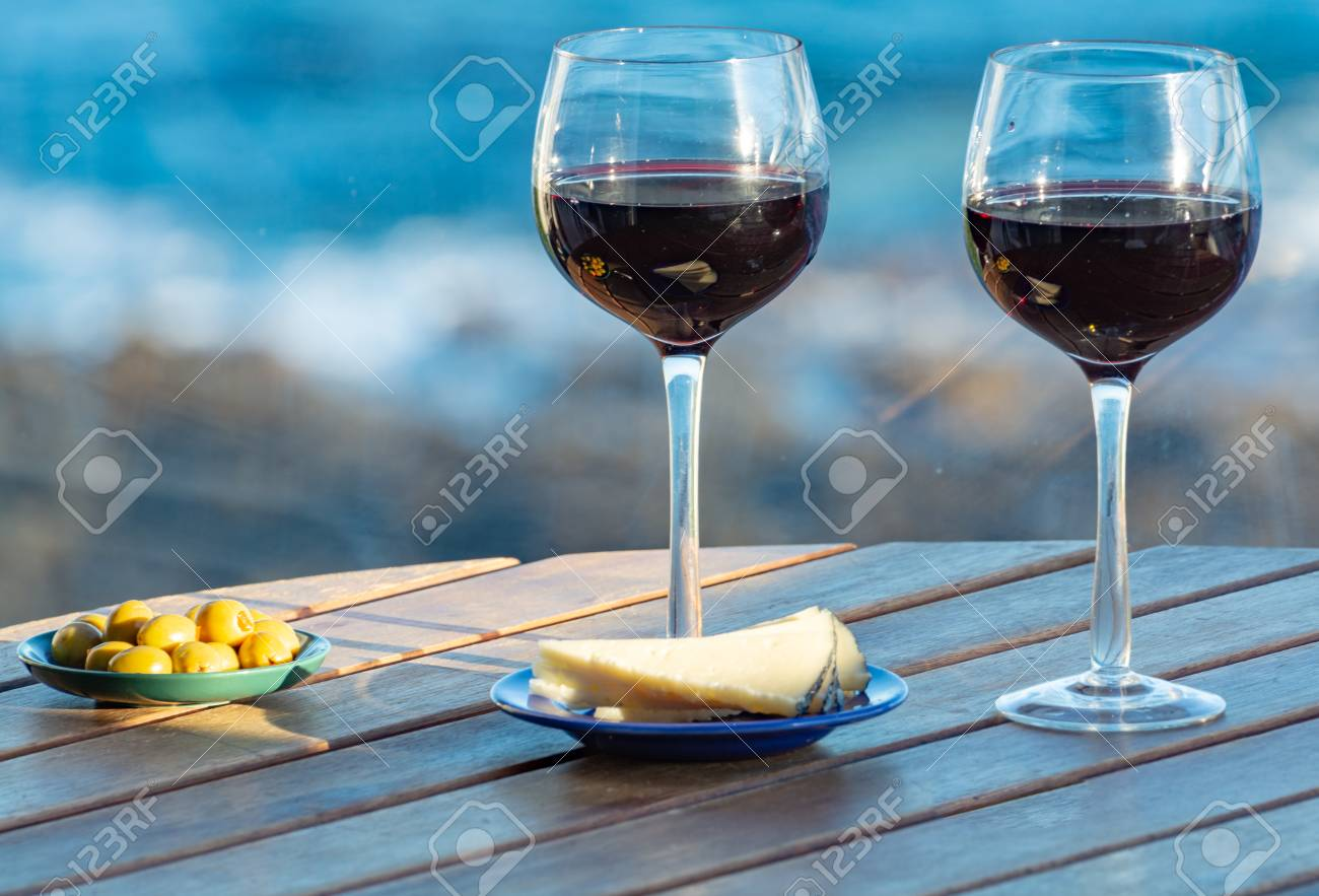 Aperitif, red wine in glasses served with cheese and olives on outdoor tessace witn sea view close up - 113774079