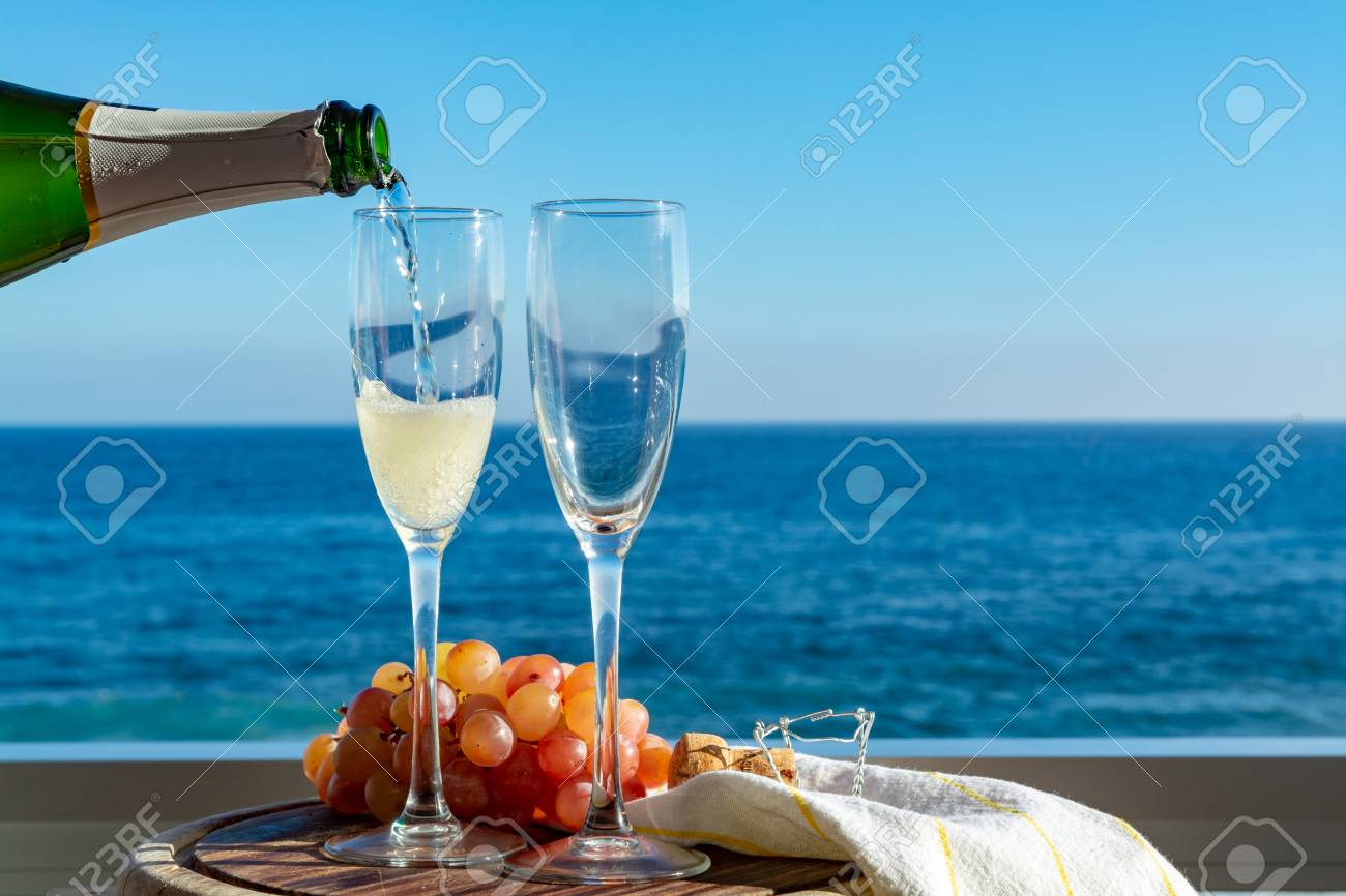 Waiter pouring Champagne, prosecco or cava in two glasses on outside terrace with sea view close up - 113774086