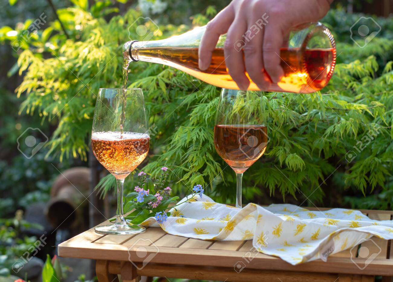 Waiter pouring cold rose wine in glasses on outdoor terrace in garden in sunny day - 118593095