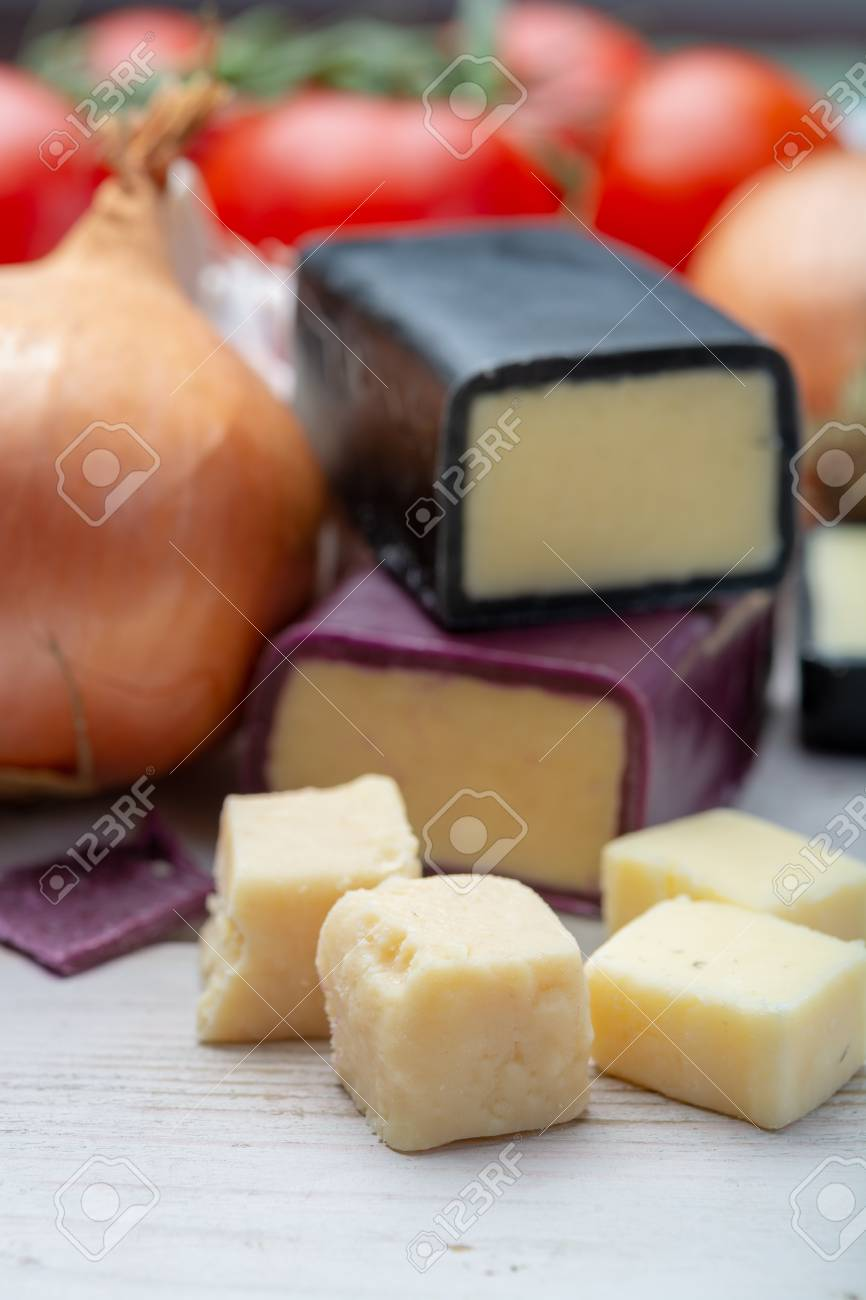 Mini black and dark red waxed cheddar cheeses with strong flavor