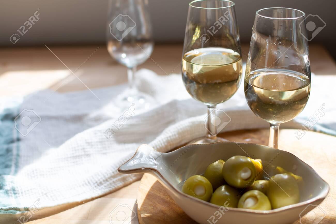 Sherry wine tasting, dry fino, manzanilla or palomino jerez fortified wine in glasses, Jerez de la Frontera, Andalusia, Spain close up - 136359873